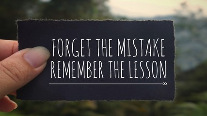 Motivational and inspirational quote - 'Forget the mistake, remember the lesson' written on a black paper. Vintage styled background.