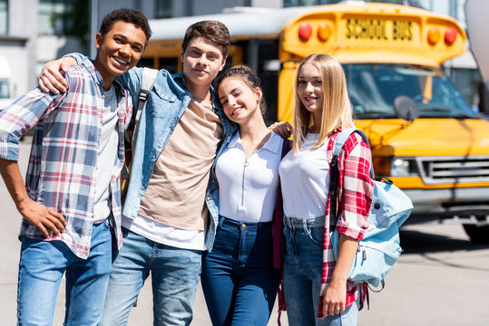 group of teen smiling scholars looking at camera and embracing while standing in front of school bus