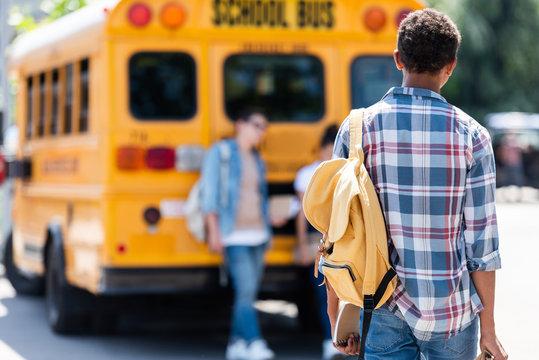 rear view of teen schoolboy walking to classmates leaning on school bus