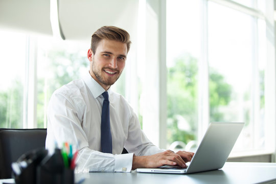 Happy young businessman using laptop at his office desk