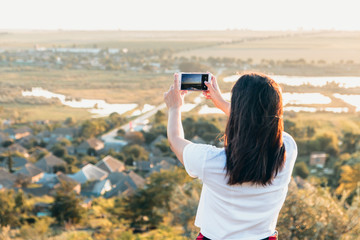 Beautiful girl taking pictures of coutryside from a hill at sunset