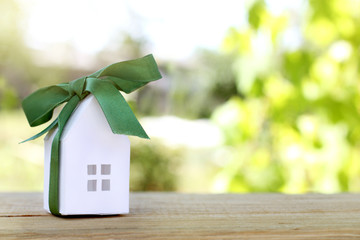 desirable gift dreams for summer stay/ layout houses, in a festive green bow on the backdrop of garden
