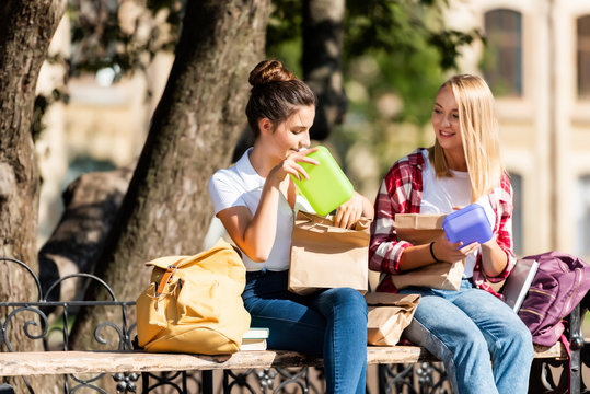 happy teen schoolgirls sitting on bench with lunch boxes