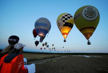 Judges watch competitors approaching a target during the FAI World Hot Air Balloon Championship near Gross-Siegharts