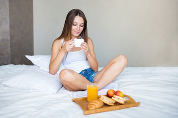 beautiful brunette girl eating a healthy breakfast and drinking coffee in bed