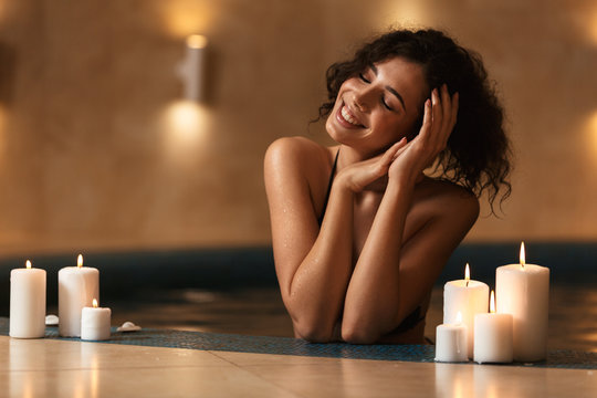 Cheerful happy beautiful woman in spa lies resting with candles.