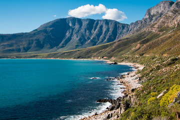 Landscape of the shoreline with the sea and mountains, blue sky and clouds in Cape Town South Africa.