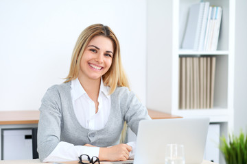 Young business woman or student girl working at office workplace with laptop computer