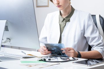 Female physician at modern medical doctor office. Woman examining x-ray at workplace in front of a desktop computer