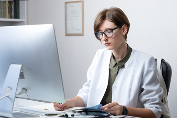 Female practitioner working at modern medical doctor office. Young medical doctor taking notes at workplace in front of a desktop computer