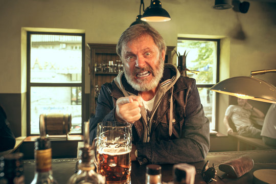 Angry bearded man drinking alcohol in pub and watching a sport program on TV. Enjoying my favorite teem and beer. Man with mug of beer sitting at table. Football or sport fan. Human emotions concept
