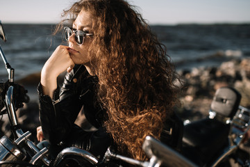 attractive curly female biker in sunglasses sitting on motorbike Wall mural