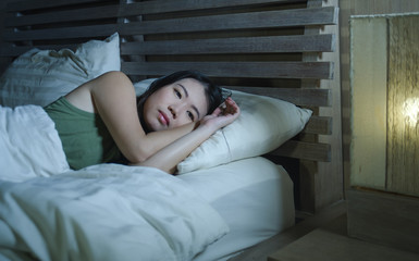 young beautiful depressed and sad Asian Chinese woman having insomnia lying in bed at night sleepless suffering anxiety stress and depression