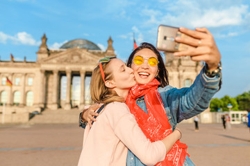Two happy woman making selfie on background of Reichstag Bundestag building in Berlin. Travel and love concept in Europe