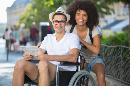 handicapped man in wheelchair and girlfriend on holidays