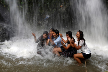 Women pose under a waterfall as their friend takes picture of them at Tokha, outskirts of Kathmandu