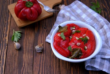 Appetizer, roasted pickled sweet red pepper in a white bowl on a wooden background. Serbian cuisine.