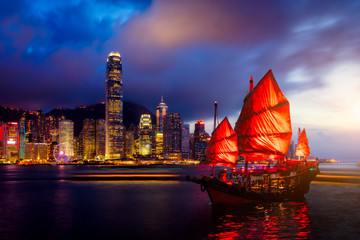 Fototapete - Hong Kong City skyline with tourist sailboat at night. View from across Victoria Harbor Hong Kong.