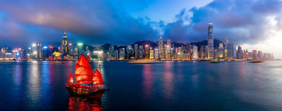 Panorama of Hong Kong City skyline with tourist sailboat at night. View from across Victoria Harbor HongKong.