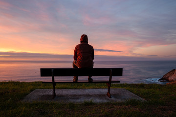 Lonely man sits alone on the rocky coast and enjoying sunset. View over rocky cliff to ocean horizon Wall mural