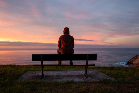 Lonely man sits alone on the rocky coast and enjoying sunset. View over rocky cliff to ocean horizon