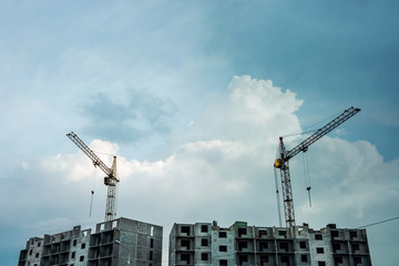 Cranes above unfinished gray multistorey panel building on background of cloudy blue sky with copy space. Process of construction of apartment building in overcast weather close up.