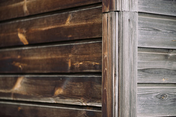 Angle of wall of rural house from horizontal planked wood. Detail fragment of vintage natural wooden texture with copy space. Natural structure of woods. Background from edge of uneven wooden wall.
