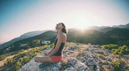 A girl is sitting on top of a mountain and smiling.