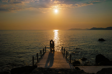 Perspective view of a wooden pier on the pond at sunset, Happy couple romantic sunset wooden Jetty pier at Fethiye Turkey vacation