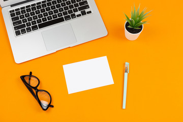 Freelancer or blogger desktop. Home office. Laptop and stationery supplies on orange background.