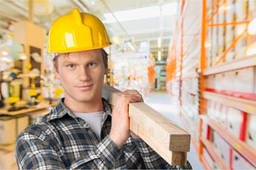 Young builder in hardhat on blurred construction materials store