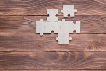Incomplete wooden puzzles on brown wooden desk, top view, flat lay.