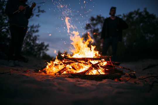 Beach summer bonfire with flames and sparks flying around