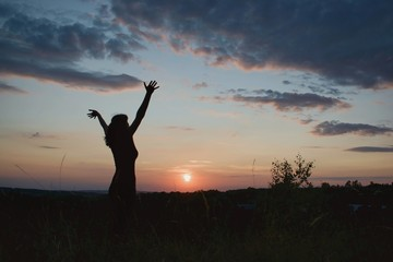 Young woman  in sunset light. Nature, outdoor, freedom, success, happiness concept