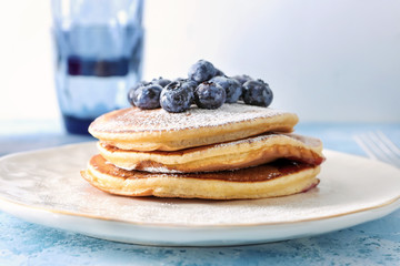 Plate with tasty pancakes and blueberries on table, closeup