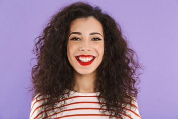 Photo closeup of beautiful young woman with curly hair in summer wear smiling to you, isolated over violet background in studio