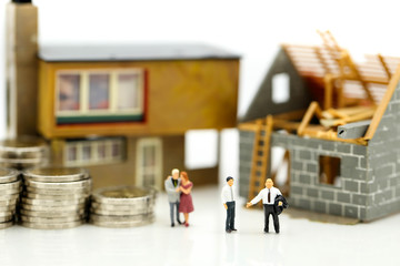 Miniature people : Business meeting with coins stack and home renovating,Business planning and Financial Concept.