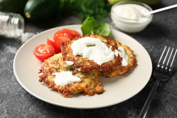 Plate with zucchini pancakes and sauce on table