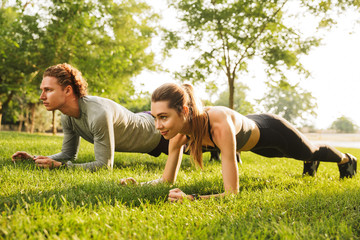 Photo of young caucasian sporty man and woman 20s in tracksuits, doing plank together on grass while training in green park during sunny summer day