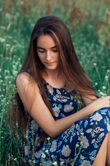 pretty teenager girl with healthy long hair sitting on the meadow in summer day