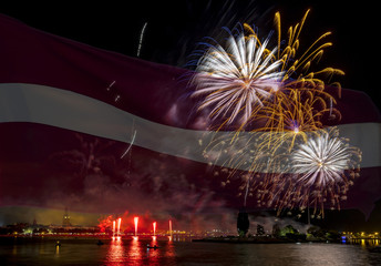 Conceptual collage image symbolizing 100 years of Latvian State Independence. Flag of Latvia on background of festive firework above old Riga