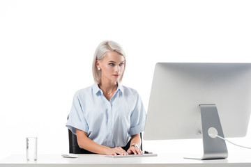 portrait of businesswoman working on computer at workplace with glass of water isolated on white