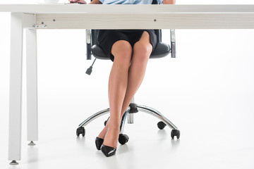 partial view of businesswoman in skirt and black high heels sitting at workplace isolated on white