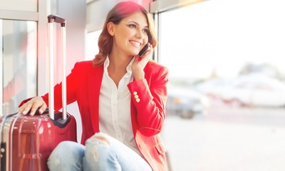 Airport business woman on smart phone at gate waiting in