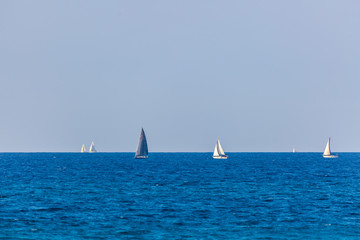Six yachts with white and gray sails on Mediterranean Sea