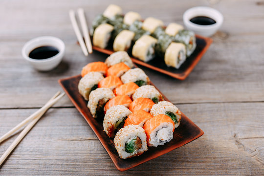 Japanese restaurant, traditional cuisine. Appetizing set of sushi rolls served on clay plates, chopsticks and sauce bowls