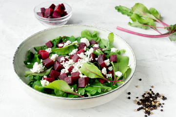 Healthy salad - boiled beetroot with goat cheese and arugula on concrete table.