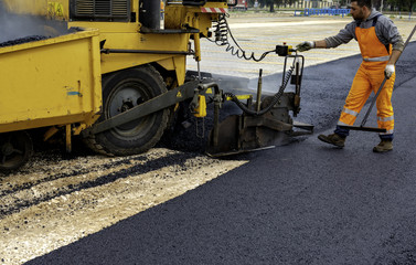 Machine operator to spread asphalt, intervenes on the control panel to adjust the asphalt paving