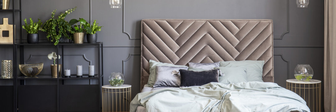 Bed with headboard between gold tables in grey bedroom interior with plants. Real photo
