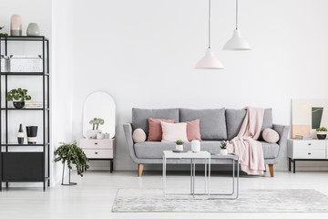 Real photo of a living room interior with a sofa, pillows, tables, black shelf and lamps